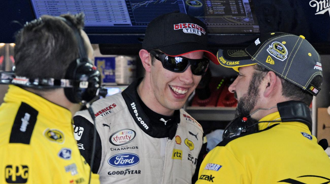 Brad Keselowski, center, talks to crew members during practice for Saturday's NASCAR Sprint Cup Series auto race at Charlotte Motor Speedway in Concord, N.C., Friday, Oct. 9, 2015. (AP Photo/Mike McCarn)