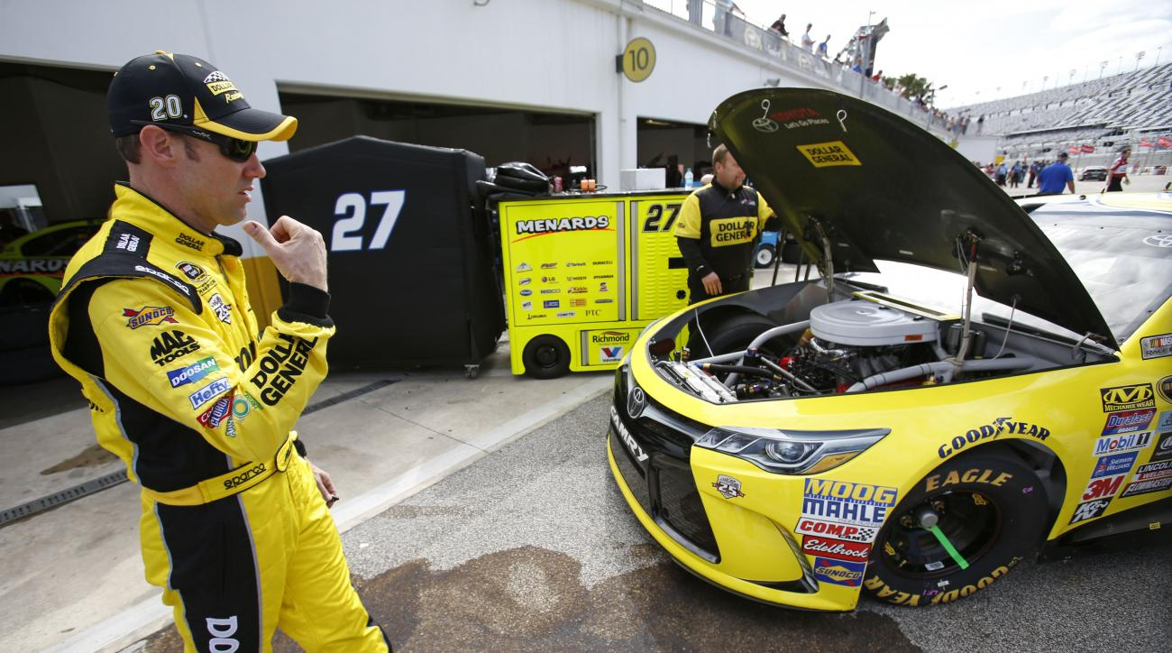 Matt Kenseth directs team members working on his car during practice for Sunday's NASCAR Daytona 500 Sprint Cup series auto race at Daytona International Speedway in Daytona Beach, Fla., Friday, Feb. 19, 2016. (AP Photo/Wilfredo Lee)