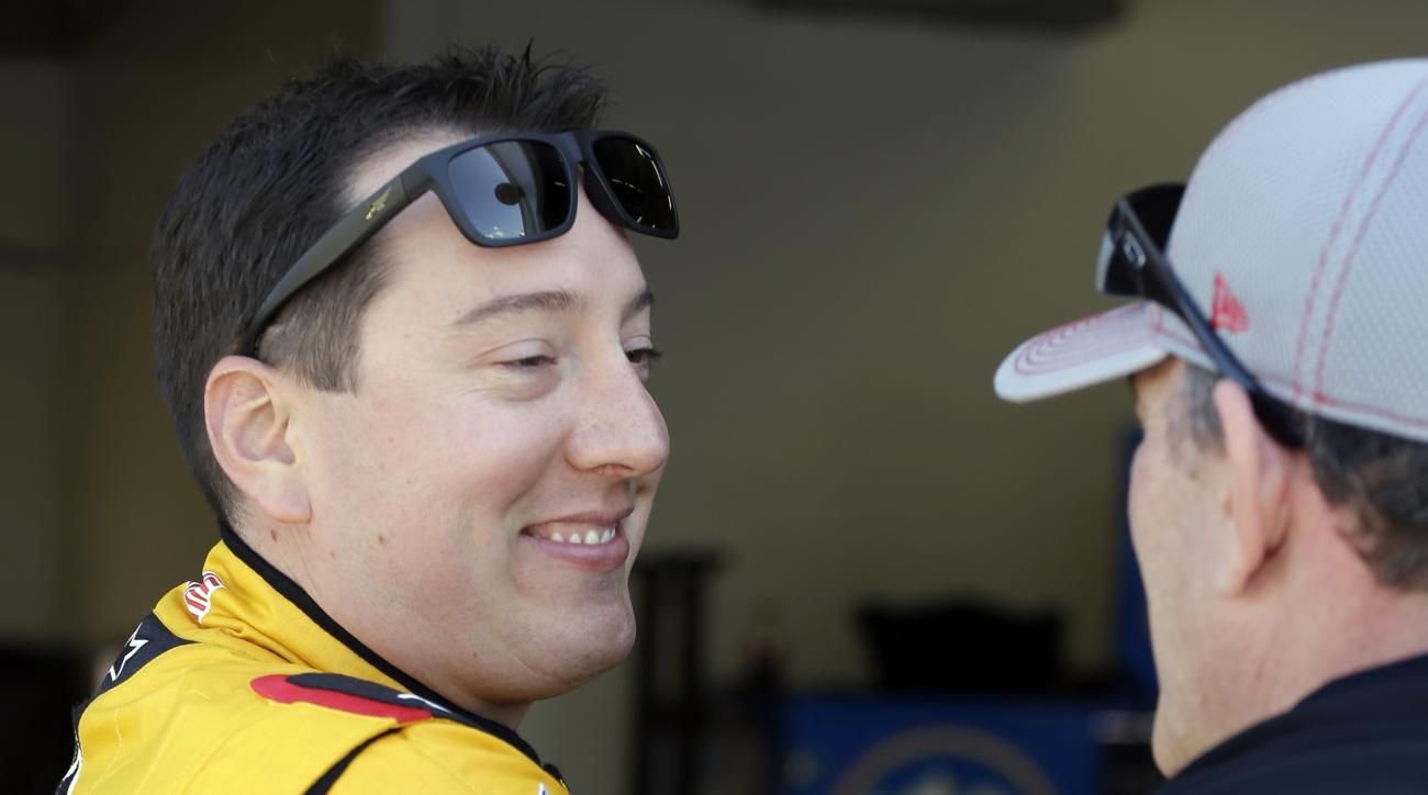 Kyle Busch, left, talks to a crew member during practice for Sunday's NASCAR Daytona 500 Sprint Cup series auto race at Daytona International Speedway in Daytona Beach, Fla., Friday, Feb. 19, 2016. (AP Photo/Terry Renna)