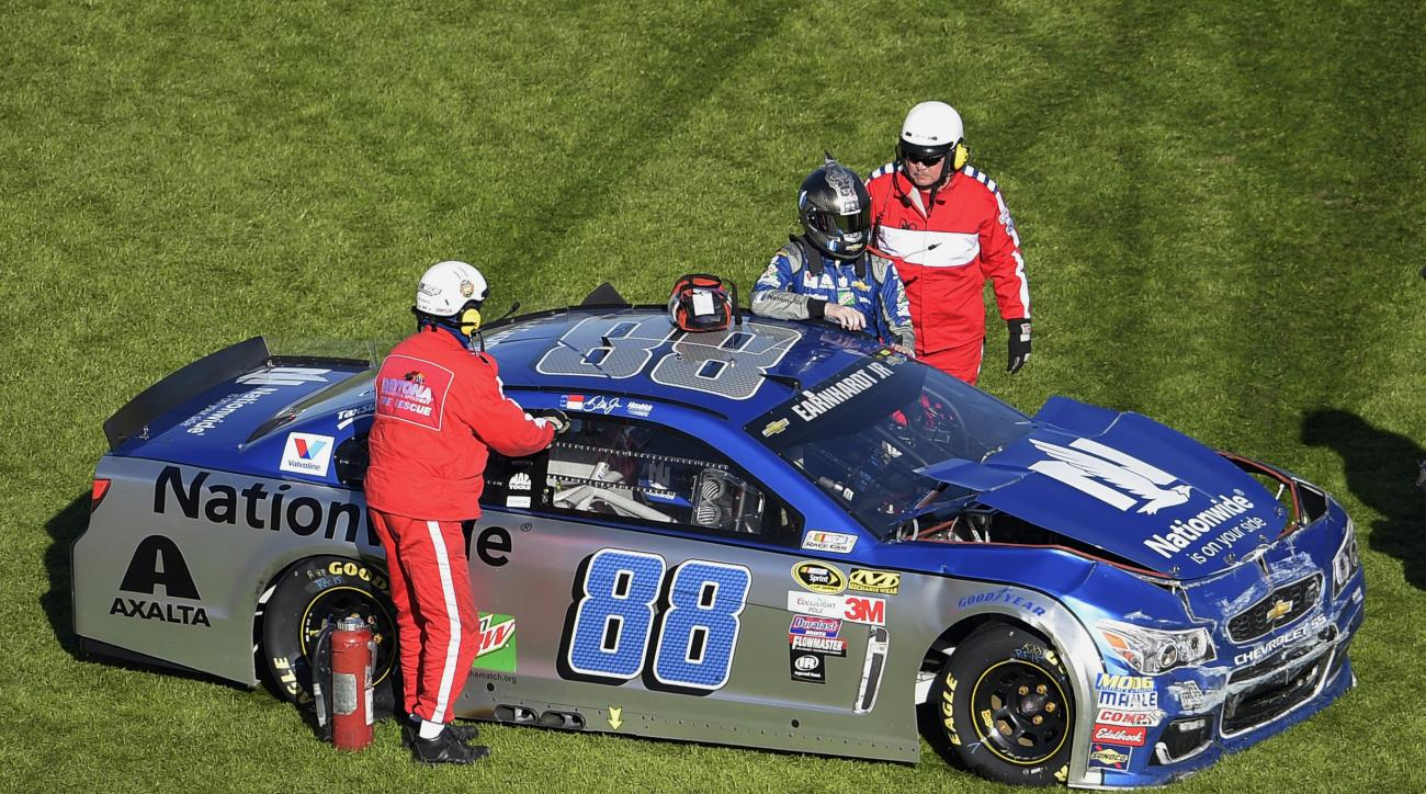 Dale Earnhardt Jr. (88) is helped out of his car after hitting an interior wall as he was losing control of his car, coming out of Turn 4 during the NASCAR Daytona 500 Sprint Cup series auto race at Daytona International Speedway, Sunday, Feb. 21, 2016, i