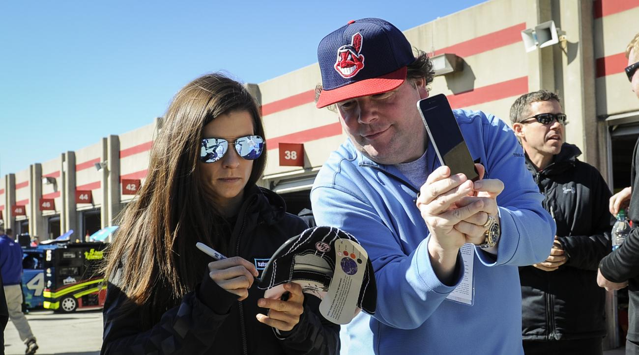 Danica Patrick, left, signs an autograph for a fan during practice at Atlanta Motor Speedway Saturday, Feb. 27, 2016, in Hampton, Ga., for Sunday's NASCAR Sprint Cup Series auto race. (AP Photo/John Amis)