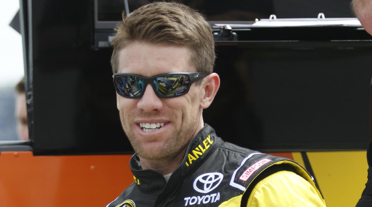 Carl Edwards smiles while standing in pit row during qualifying for the NASCAR Sprint Cup Series auto race at Texas Motor Speedway in Fort Worth, Texas, Friday, April 8, 2016. Edwards took the pole position for the 20th Annual Duck Commander 500 that runs