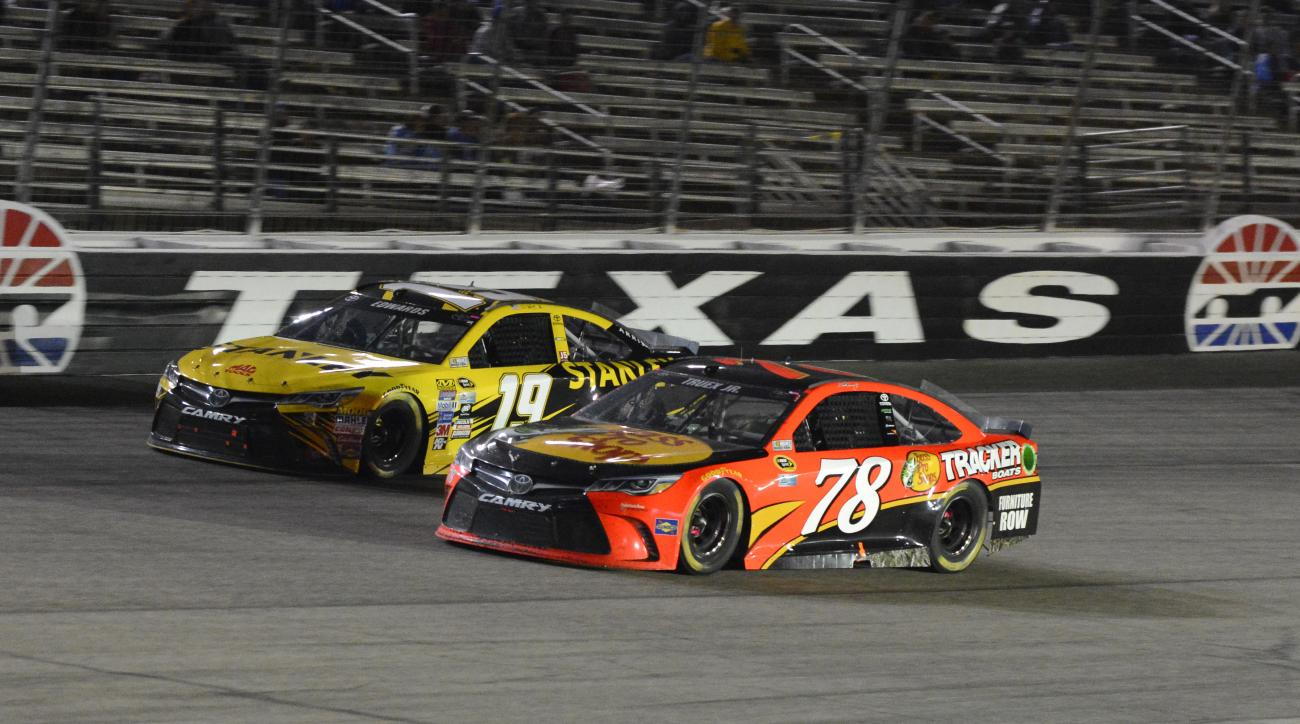 Martin Truex Jr. (78) drives next to Carl Edwards (19) during the NASCAR Sprint Cup Series auto race at Texas Motor Speedway in Fort Worth, Texas, Saturday, April 9, 2016. (AP Photo/Larry Papke)