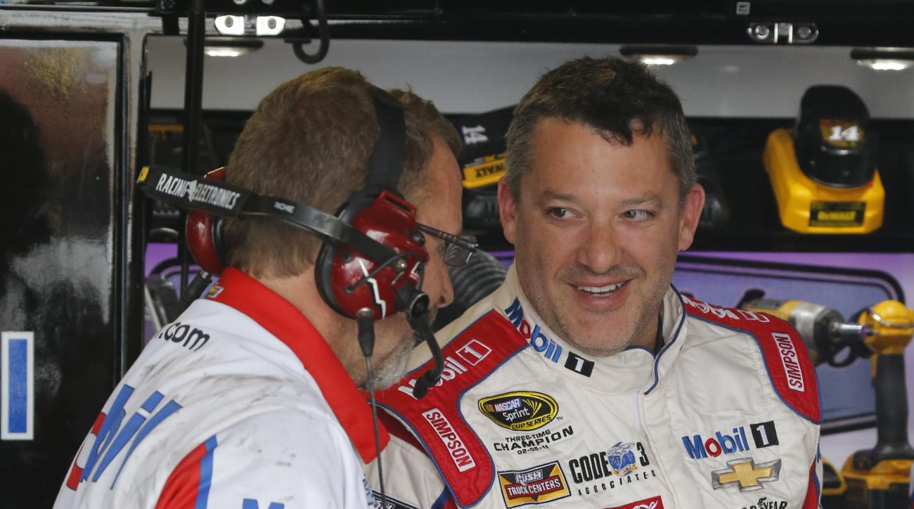 Tony Stewart, right, jokes with a crew member during practice for Sunday's NASCAR Sprint Cup auto race at Richmond International Raceway in Richmond, Va., Friday, April 22, 2016. Stewart is making his return to Sprint Cup racing after a preseason injury.