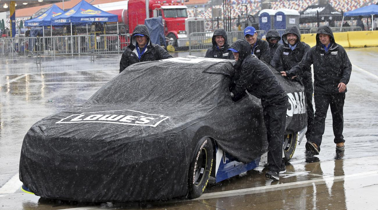 Crew members push driver Jimmie Johnson's car through the garage area at Charlotte Motor Speedway in Concord, N.C., Friday, May 20, 2016 before the scheduled start of the NASCAR Sprint Showdown auto race later today. Activities at the track have been dela