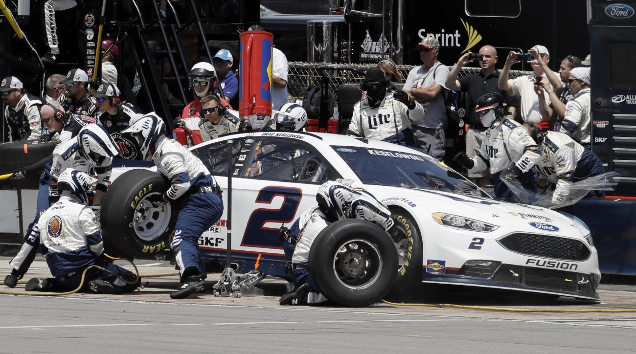 Crew members work on the car of Brad Keselowski during a pit stop in the NASCAR Sprint Cup series auto race at Pocono Raceway, Monday, June 6, 2016, in Long Pond, Pa. (AP Photo/Matt Slocum)