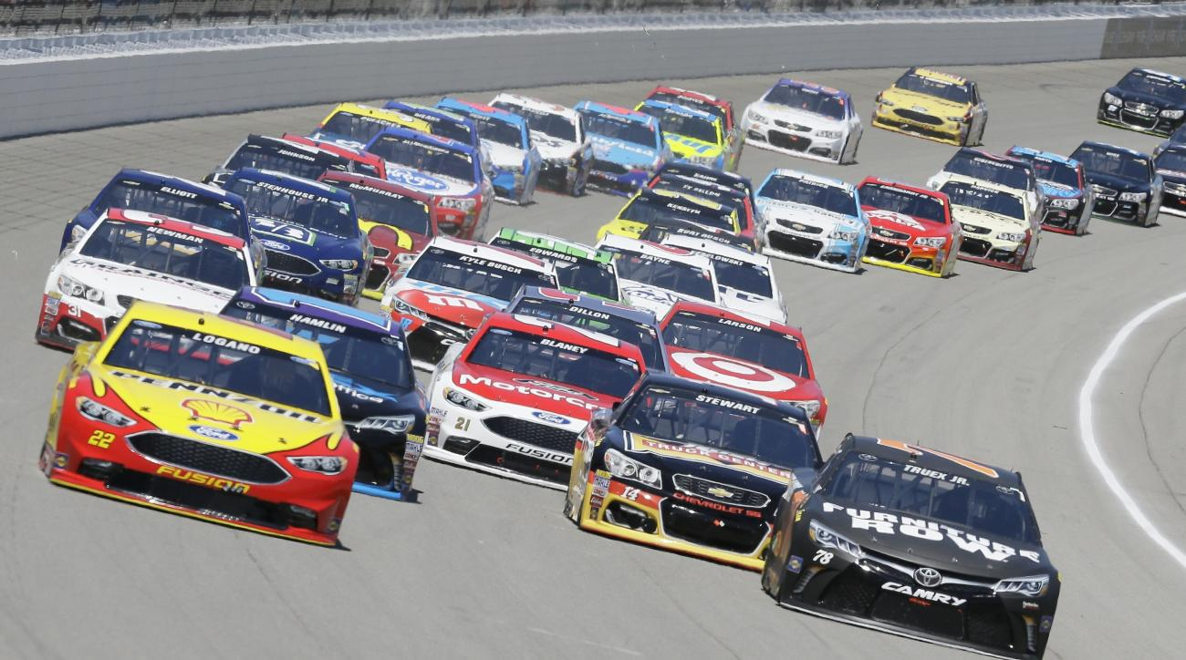 Joey Logano, left, and Martin Truex Jr., right, lead the field during the NASCAR Sprint Cup series auto race at Michigan International Speedway, Sunday, June 12, 2016, in Brooklyn, Mich. (AP Photo/Carlos Osorio)