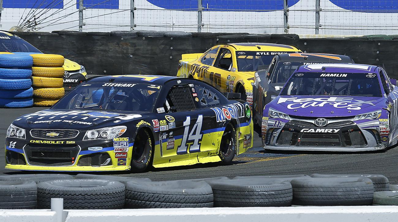 Tony Stewart, left, leads Denny Hamlin through Turn 11 during the NASCAR Sprint Cup Series auto race Sunday, June 26, 2016, in Sonoma, Calif. (AP Photo/Ben Margot)