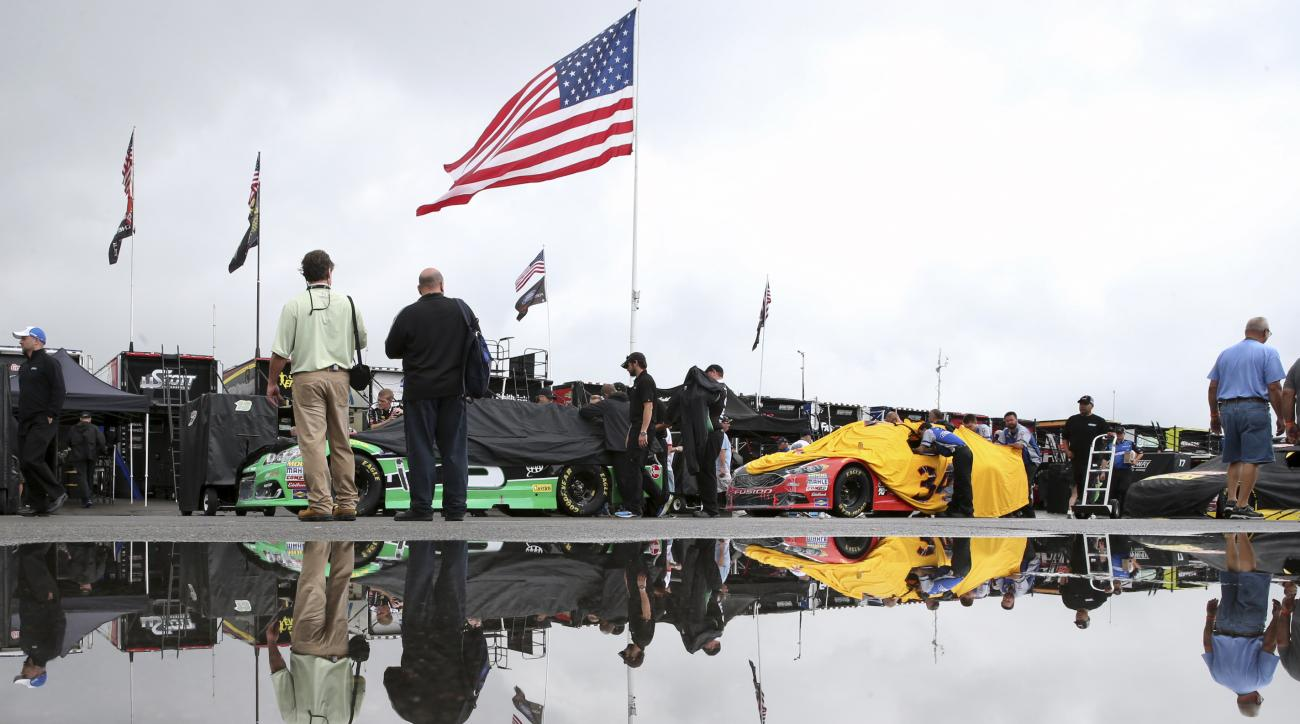 Race cars are lined up for inspection in the rain in the garage area at Pocono Raceway before the NASCAR Sprint Cup Series Pennsylvania 400 auto race Sunday, July 31, 2016, in Long Pond, Pa. (AP Photo/Mel Evans)