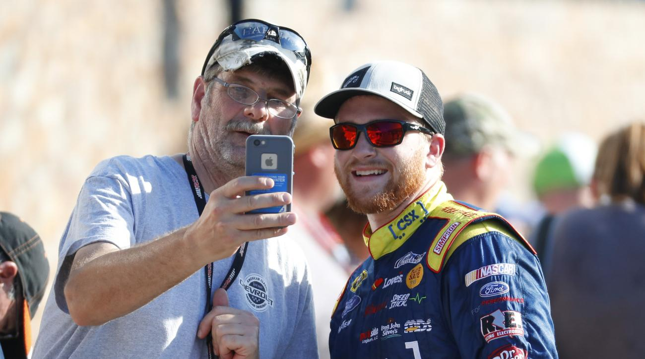 Chris Buescher smiles for a photograph with a fan after  qualifications for the NASCAR Sprint Cup Series auto race at Michigan International Speedway, in Brooklyn, Mich., Friday, Aug. 26, 2016. (AP Photo/Paul Sancya)
