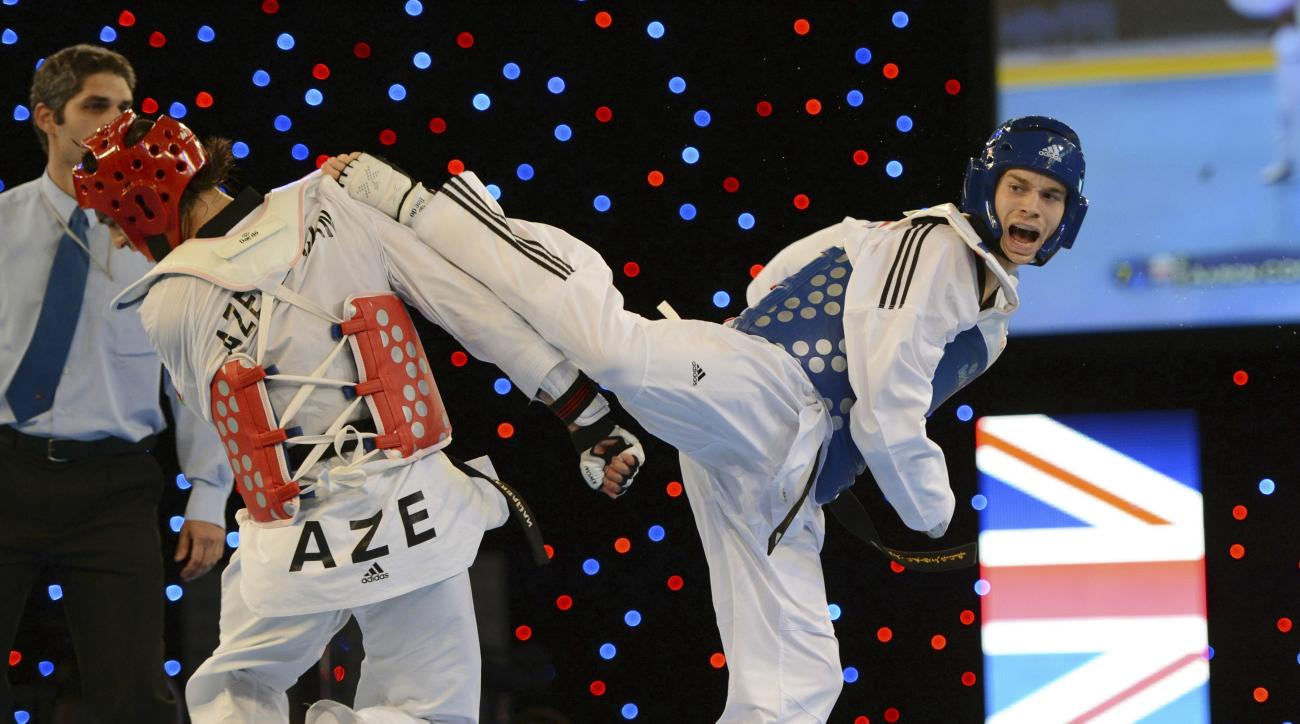 FILE - This is a Saturday May 5, 2012 file photo of Britain's Aaron Cook, right, as he aims a kick on his way to controversially beating Ramin Azizov of Azerbaijan in the final of the Men's -80kg competition during the European Taekwondo Championships, at