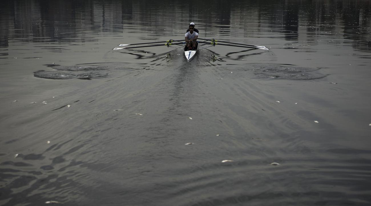 Rowing athletes Diego Nazario, back, and Emanuel Dantas Borges, train in the Rodrigo de Freitas lagoon, surrounded by dead small silvery fish, in Rio de Janeiro, Brazil, Thursday, April 16, 2015. Rio de Janeiro's waste management company is still cleaning