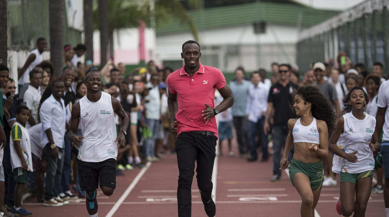 Jamaican Olympic gold medalist Usain Bolt, center, playfully races with youths during a visit to a social sport program at Mangueira slum in Rio de Janeiro, Brazil, Thursday, April 16, 2015. (AP Photo/Felipe Dana)