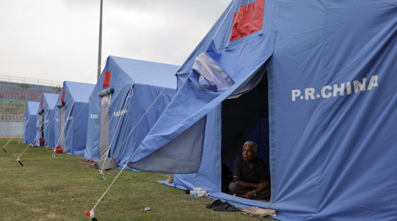 In this Saturday, May 16, 2015 photo, a Nepalese man watches from inside a makeshift tent set for earthquake survivors at Dasharath Stadium in Kathmandu, Nepal. Two recent earthquakes killed more than 8,300 people and have had a devastating impact on all