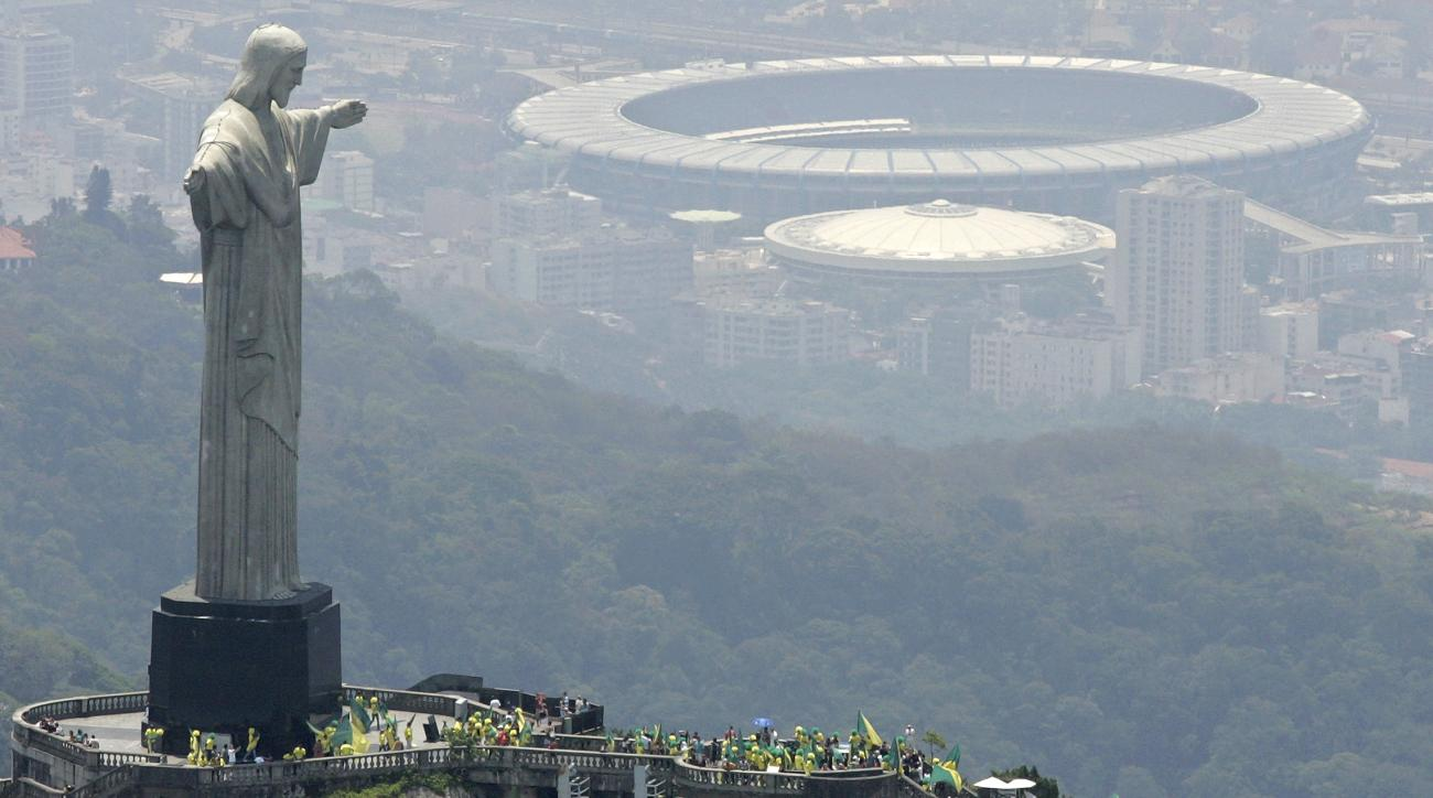 FILE - In this Oct. 30, 2007 file photo, people wave flags at the foot of the statue Christ the Redeemer on Corcovado mountain in Rio de Janeiro, after Brazil was officially chosen by FIFA as the host country for the 2014 World Cup. Mayor Eduardo Paes exp