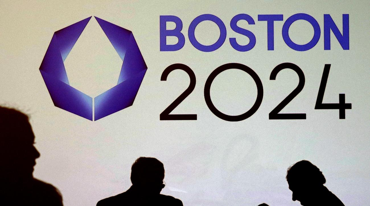 FILE - In this Jan. 21, 2015 file photo, shadows of organizers and reporters pass a video display screen prior to a news conference by organizers of Boston's campaign for the 2024 Summer Olympics in Boston. Public hearings debating the pros and cons of th