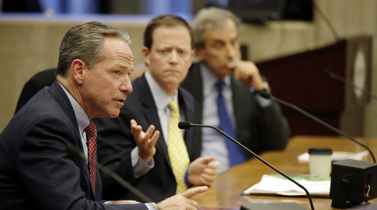 FILE - In this March 6, 2015, file photo, John Fish, chairman of Boston 2024, answers a councilman's question, as Boston 2024's CEO Richard Davey, center, and chief architect David Manfredi, right, listen, during the first meeting of the City Council on t