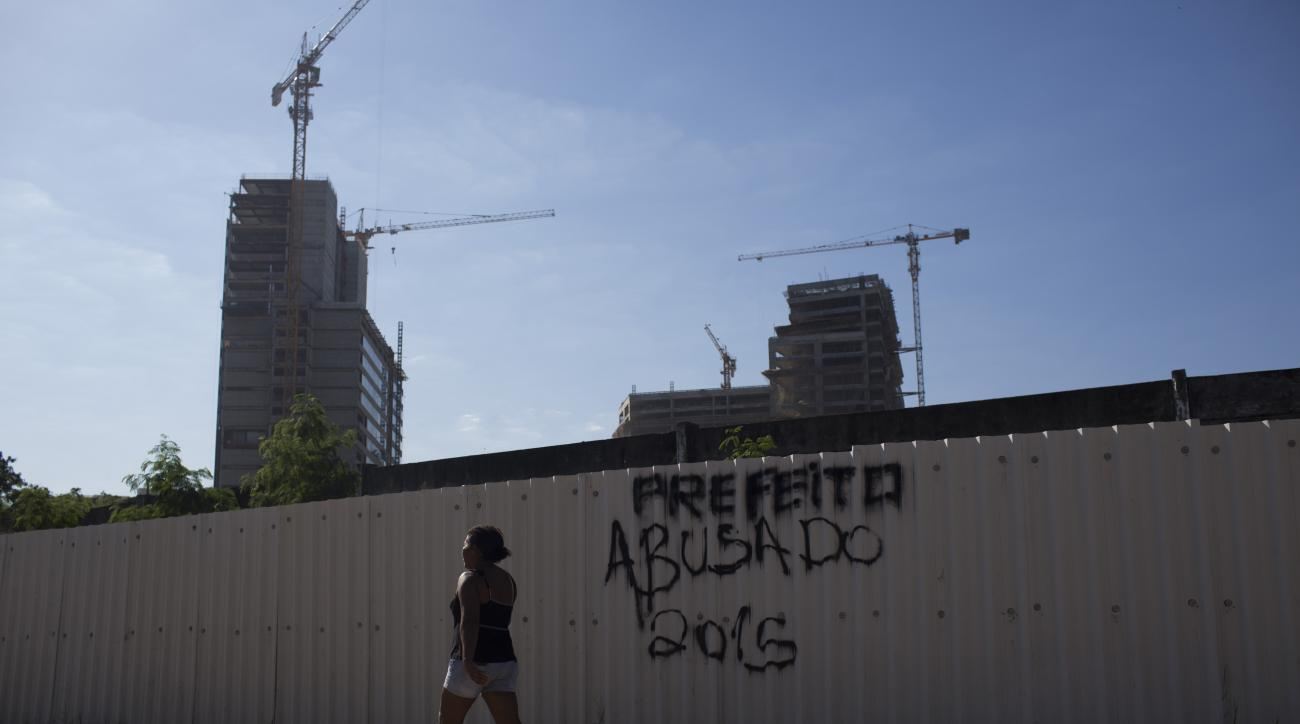 """A resident of Vila Autodromo walks past a graffiti that reads in Portuguese """"Cocky Mayor 2015"""" near the Olympic Park construction site, in Rio de Janeiro, Brazil, Tuesday, June 9, 2015. Smack up against the rising girders, on the far edge of the Olympic P"""