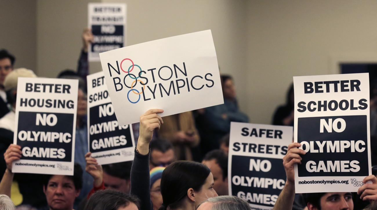 FILE - In this Feb. 5, 2015, file photo, people in the audience hold up placards against the Olympic Games coming to Boston, during the first public forum regarding the city's 2024 Olympic bid, in Boston. While Bostonians are hesitant to host the Olympics