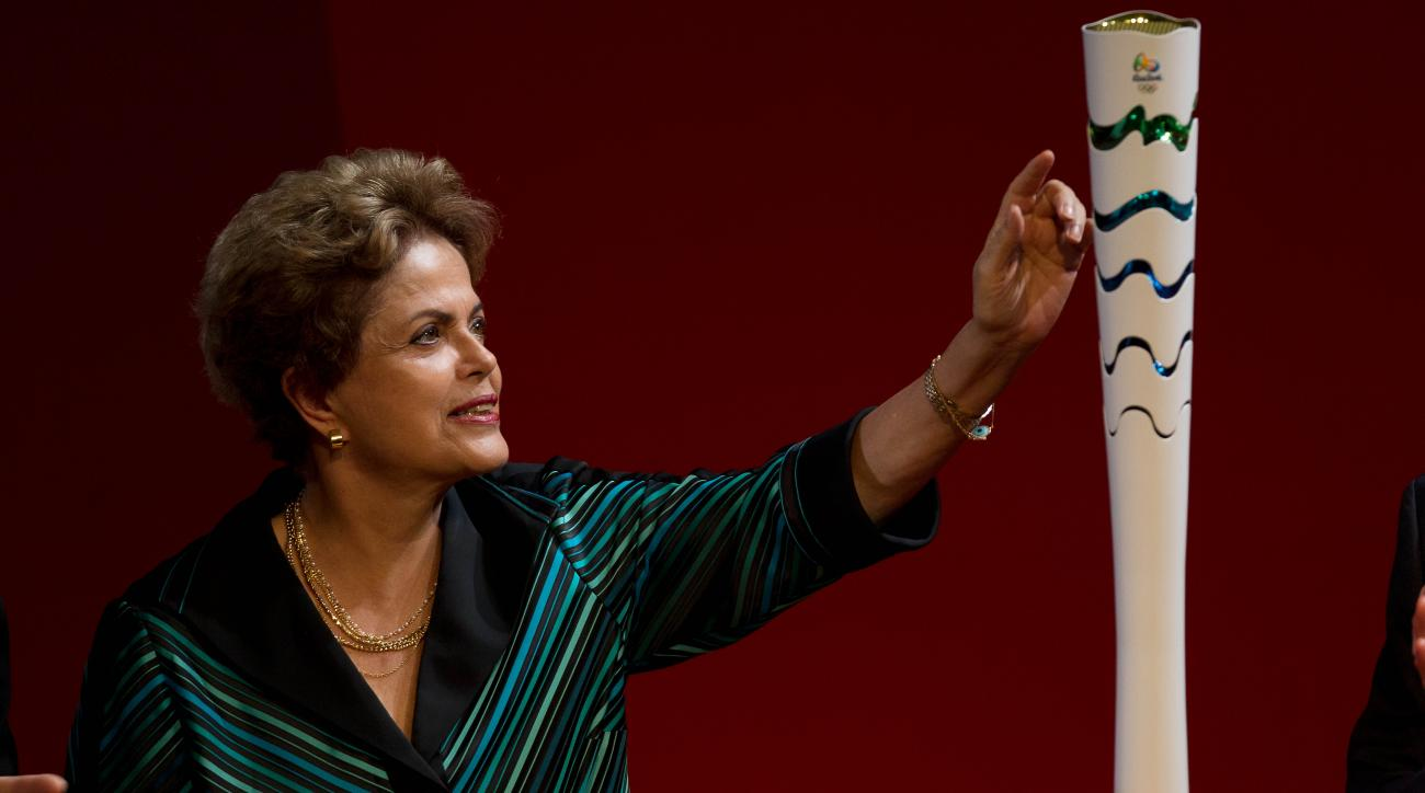 Brazil's President Dilma Rousseff looks at the Olympic Torch as it's presented during a ceremony ahead of the 2016 Rio Olympic Games in Brasilia, Brazil, Friday, July 3, 2015. Brazil will host the 2016 Summer Olympics. (AP Photo/Joedson Alves)