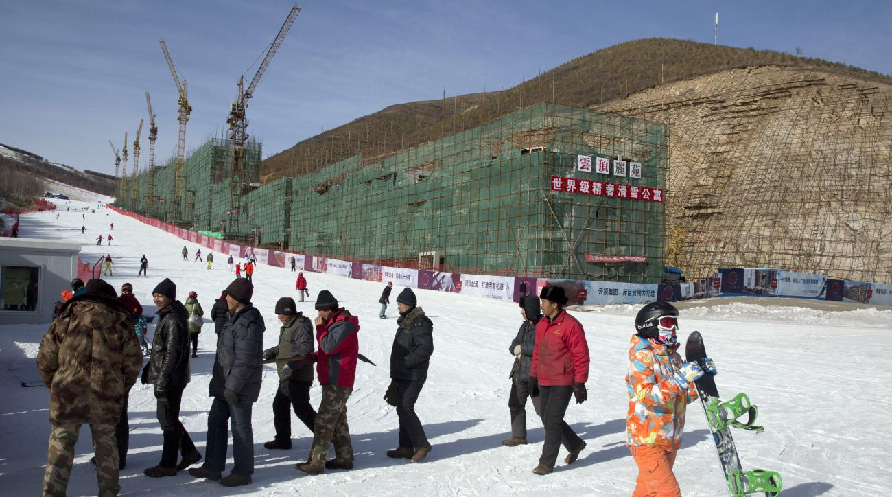 FOR STORY OLYMPICS 2022 BID - FILE - In this Saturday, Dec. 6, 2014 file photo, a snowboarder walks past migrant workers near a hotel under construction next to a ski slope at the Chongli ski resort in Hebei province where the Nordic skiing, ski jumping,