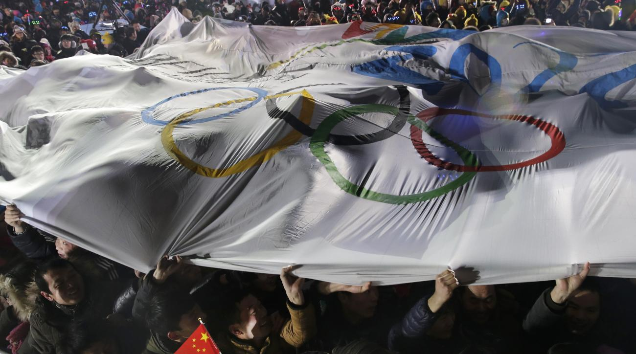 FOR STORY OLYMPICS 2022 BID - FILE - In this Jan. 1, 2015 file photo, Chinese people hold a giant banner with the logo for Beijing's Winter Olympics bid as they celebrate the New Year in front of the National Stadium during a new year's countdown event in