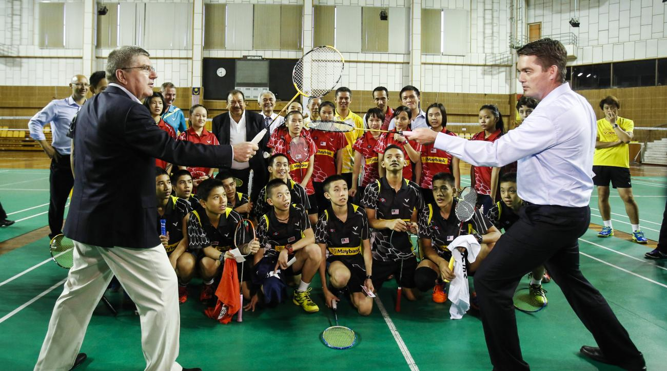 Thomas Bach, front left, president of the International Olympic Committee (IOC)  and Poul-Erik Hoyer, front right, president of the Badminton World Federation (BWF) pose for a group photo with the members of a Malaysian badminton youth team at a badminton