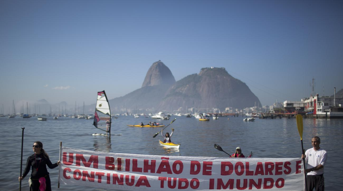 """Protesters hold a banner with a message that reads in Portuguese; """"One billion dollars and it's still disgusting"""" during a demonstration on Botafogo Beach, in the Guanabara Bay in Rio de Janeiro, Brazil, Saturday, June 6, 2015, near where Olympic sailin"""