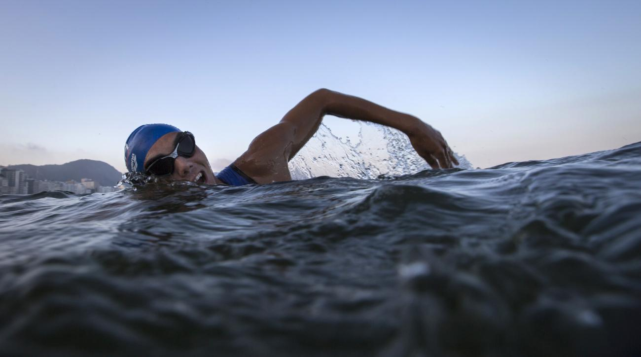 "A triathlete swims in the waters of Copacabana Beach during training in Rio de Janeiro, Brazil, Friday, July 31, 2015. Triathletes swam in the waters off Copacabana despite published warnings that water in the area was ""unfit"" for swimming. Athletes said"