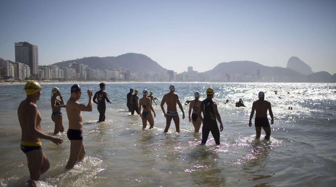People wade into the water during a clinic held by U.S. triathletes for local swimmers along Copacabana beach in Rio de Janeiro, Brazil, Monday, Aug. 3, 2015. Triathletes swam in waters off Copacabana Beach despite published warnings that water in the are