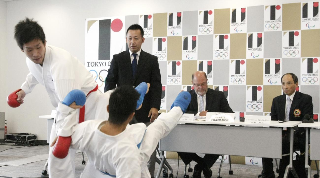 Ryutaro Araga, foreground left, and Hiroto Shinohara, foreground right, demonstrate kumite, or fighting against an opponent using punches and kicks, as World Karate Federation President Antonio Espinos, second right, and Secretary General Toshihisa Nagura