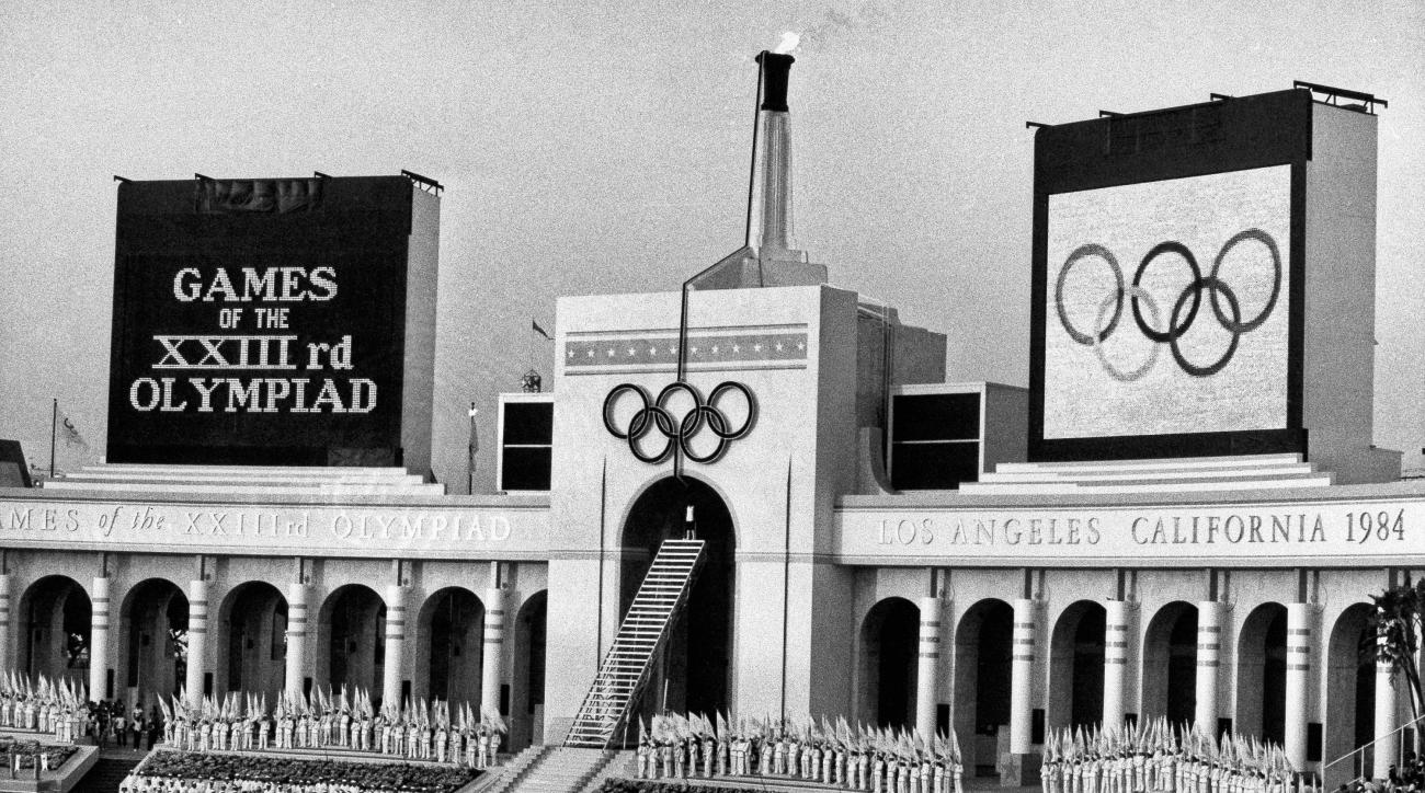 FILE - In this July 28, 1984, file photo, the Olympic flame is flanked by a scoreboard signifying the formal opening of the XXIII Olympiad after it was lit by Rafer Johnson during the opening ceremonies in the Los Angeles Memorial Coliseum. If the city of