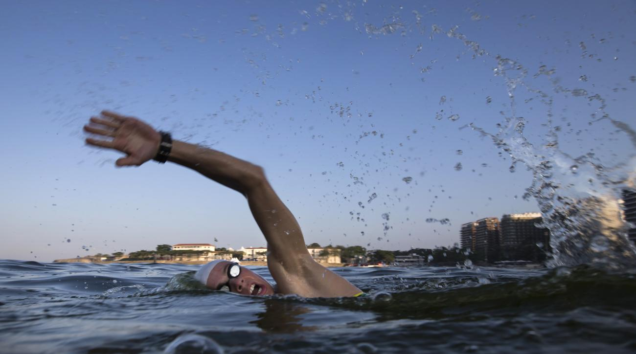 """FILE - In this July 31, 2015, file photo, a triathlete swims in the waters off Copacabana beach during training in Rio de Janeiro, Brazil. The World Health Organization's top water expert said Friday, Aug. 14, 2015, the body """"never advised against viral t"""