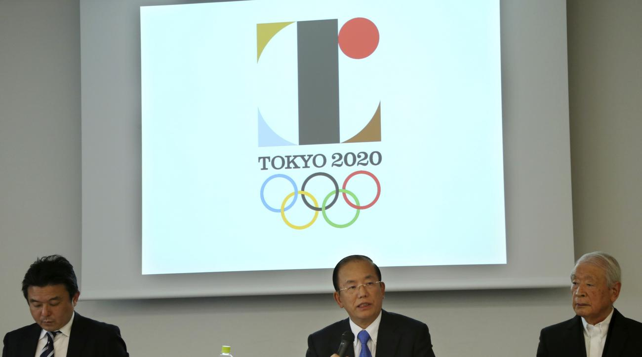 Tokyo 2020 Olympics CEO Toshiro Muto, center, speaks in front of the logo of the 2020 Games during a press conference in Tokyo, Friday, Aug. 28, 2015. Tokyo Olympic organizers defended Japanese designer Kenjiro Sano in a logo scandal, denying allegation h