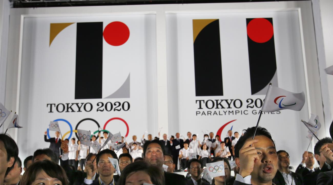 FILE - In this July 24, 2015 file photo, visitors wave flags in front of the official emblems of the Tokyo 2020 Olympics and Paralympic Games at Tokyo Metropolitan Plaza in Tokyo. Tokyo Olympic organizers are expected to scrap the logo for the 2020 Games