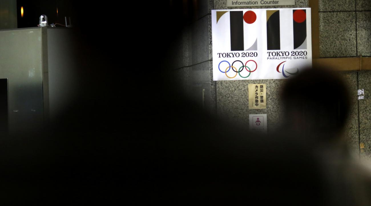 Visitors look at the logo of Tokyo Olympic Games 2020 at the Tokyo Metropolitan Government building in Tokyo Tuesday, Sept. 1, 2015.  Tokyo Olympic organizers on Tuesday decided to scrap the logo for the 2020 Games following another allegation its Japanes