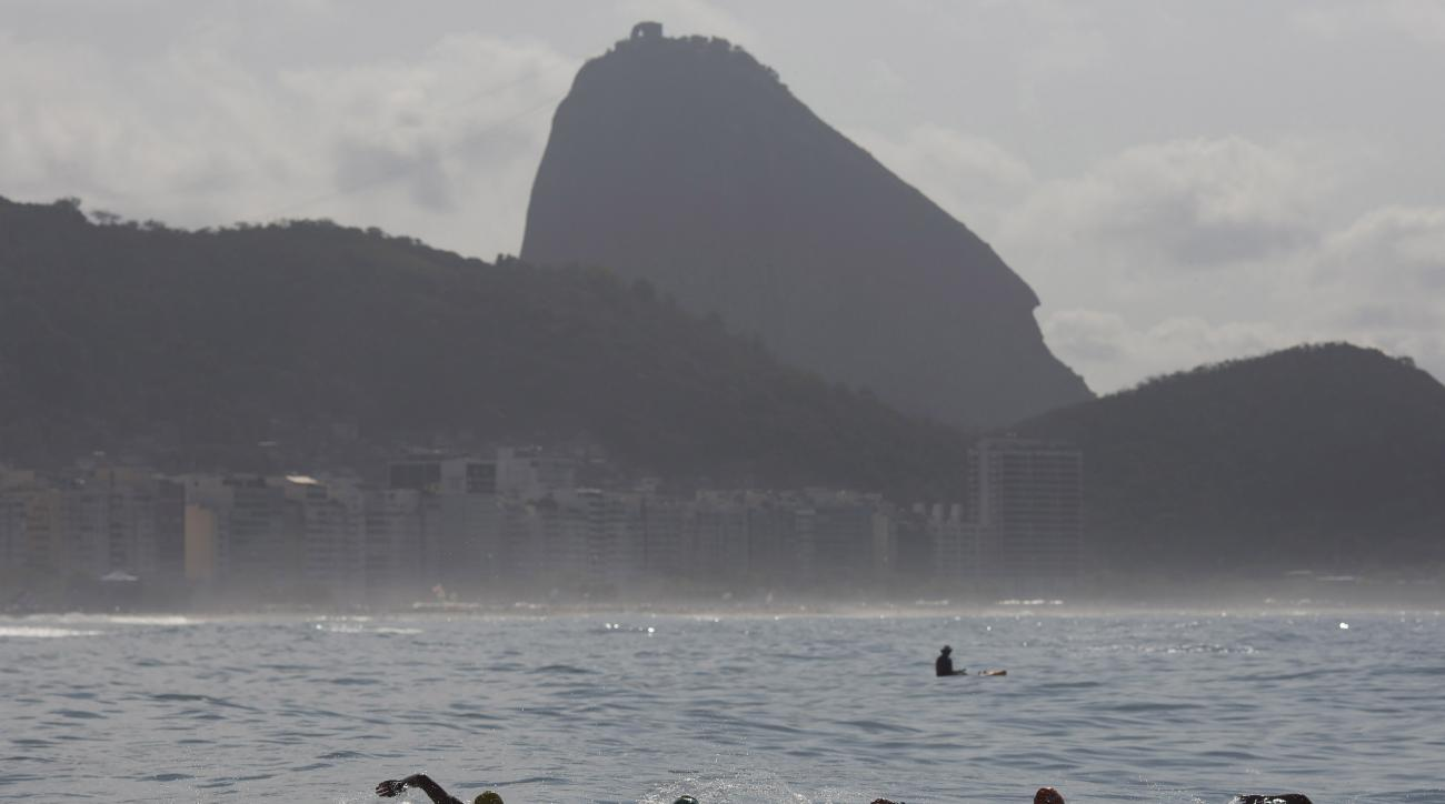 FILE - In this Aug. 22, 2015 file photo, backdropped by Sugar Loaf Mountain, athletes compete in the men's marathon swimming test event, ahead of the Rio 2016 Olympic Games, off Copacabana Beach, Rio de Janeiro, Brazil.  Swimming's world governing body FI