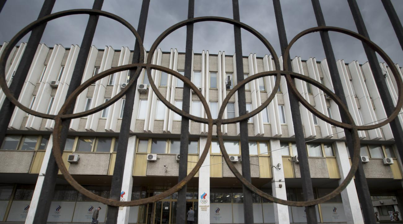 FILE - In this Nov. 13, 2015, file photo,pPeople walk in front of the Russian Olympic Committee building in Moscow. Leaders of the world anti-doping movement called for Russian track athletes to be banned from next year's Olympics, saying Monday, Nov. 16,