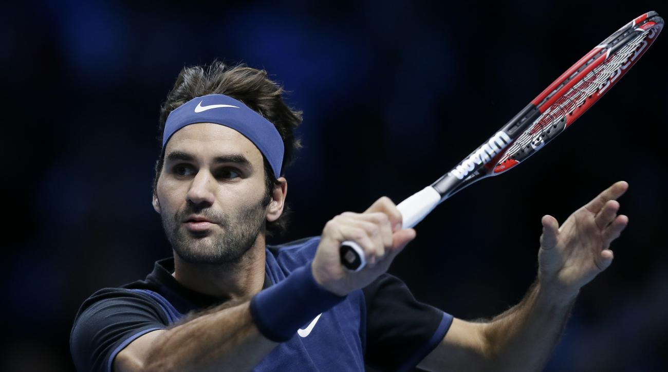 Switzerland's Roger Federer plays a return to Switzerland's Stan Wawrinka during their ATP World Tour Finals semifinal tennis match at the O2 Arena in London, Saturday Nov. 21, 2015. (AP Photo/Tim Ireland)