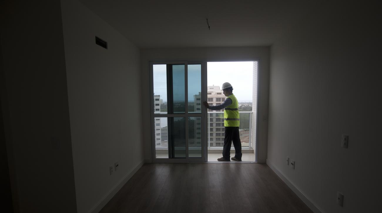 In this July 23, 2015 photo, a worker slides open a glass door of an apartment unit at Athletes Village, in Rio de Janeiro, Brazil. The 10,500 athletes at next year's Olympics will feel first-hand the deep budget cuts buffeting the Rio de Janeiro Games: t