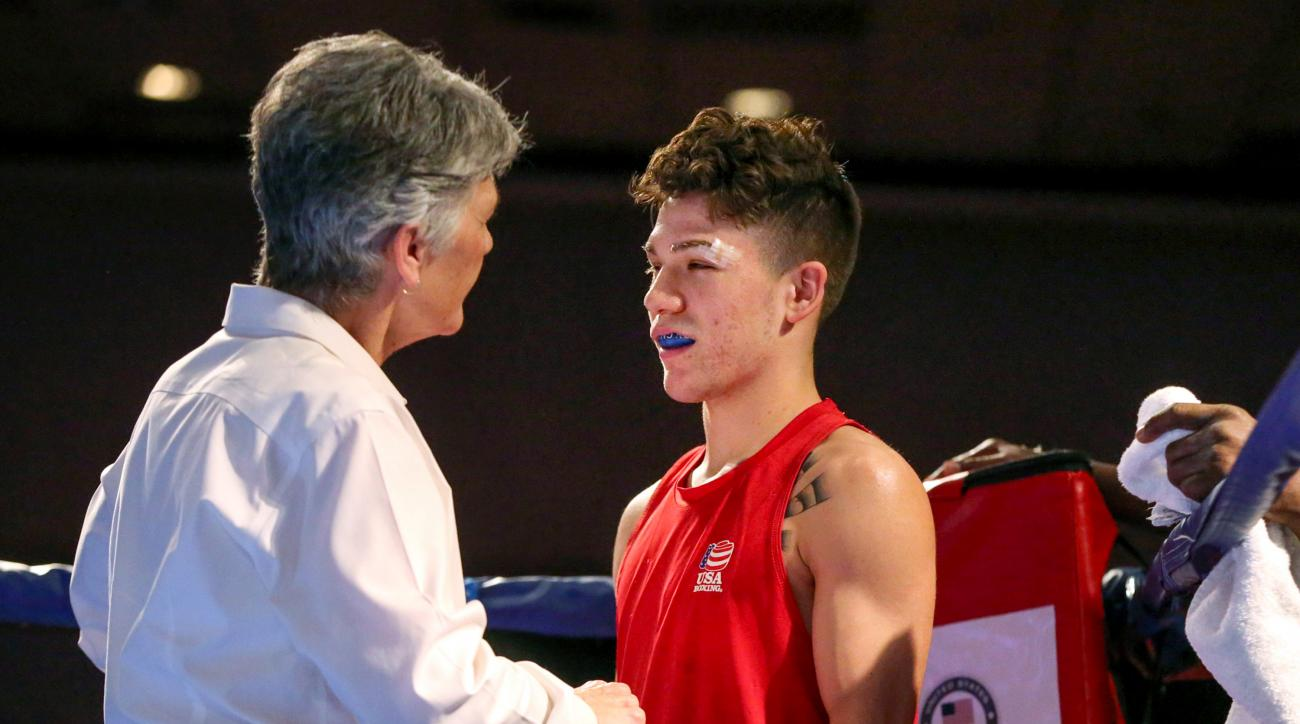 In this photo taken on Wednesday, Dec. 9, 2015, an unidentified boxing referee checks a cut on competitor Nico Hernandez prior to a bout in the U.S. Olympic Boxing Trials in Reno, Nev. Facial cuts have become a problem for many Olympic boxing hopefuls fig