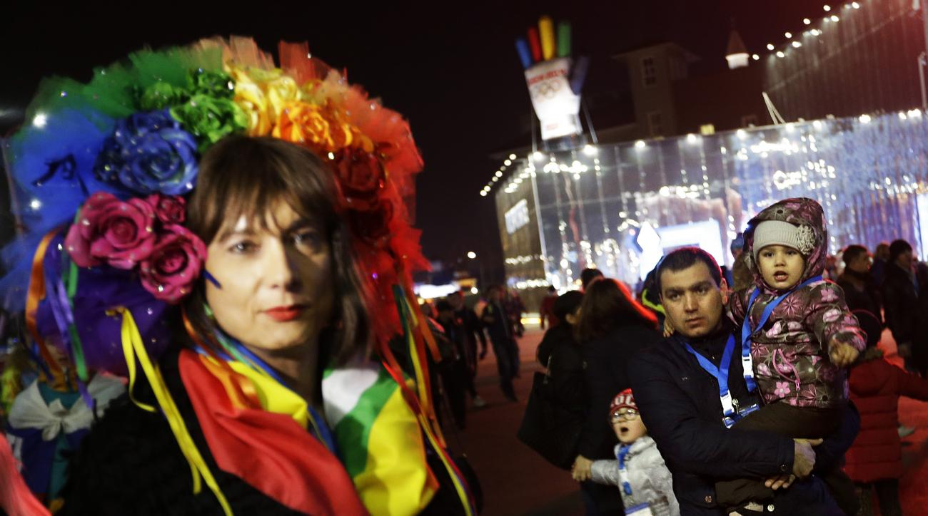 A father and children look on as Vladimir Luxuria, left, a former Communist lawmaker in the Italian parliament and prominent crusader for transgender rights, speaks out about gay rights while walking through the Olympic Plaza at the 2014 Winter Olympics,