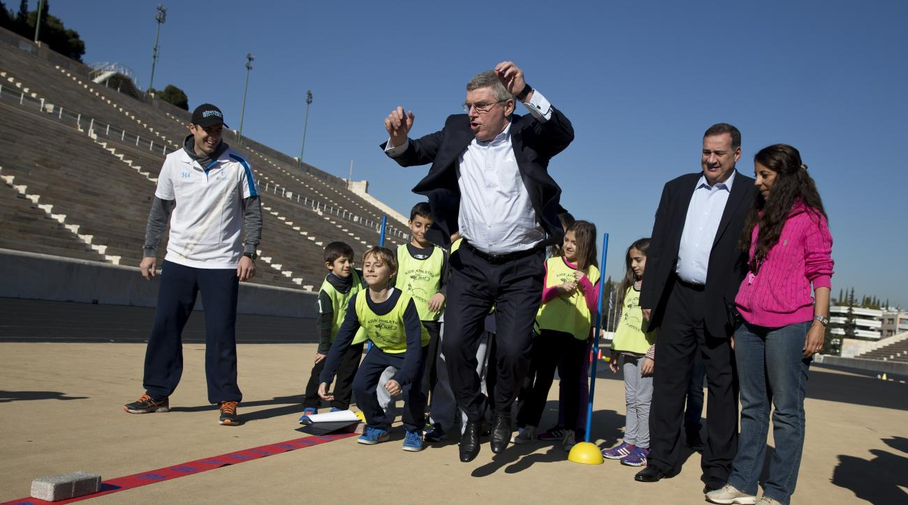 IOC President Thomas Bach plays with children during his visit at the marble Panathenian Stadium, venue of the first modern Olympics in 1896, in Athens on Friday, Jan, 29, 2016. Bach who is in Greece on a three-day visit said Thursday that a group of refu