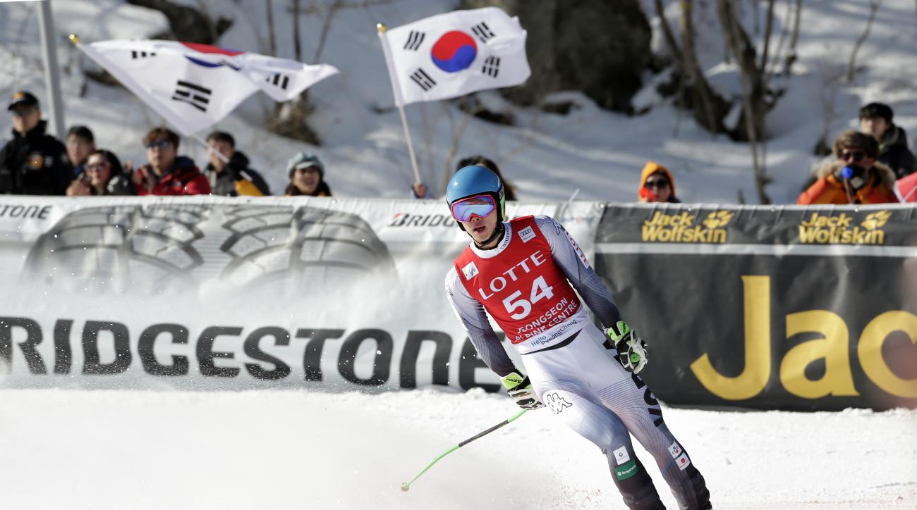 Spectators wave South Korean flags as South Korea's Kim Hyeon-tae crosses the finish line during a men's World Cup super-G race, also a test event for the Pyeongchang 2018 Winter Olympics, at the Jeongseon Alpine Centre in Jeongseon, South Korea, Sunday,
