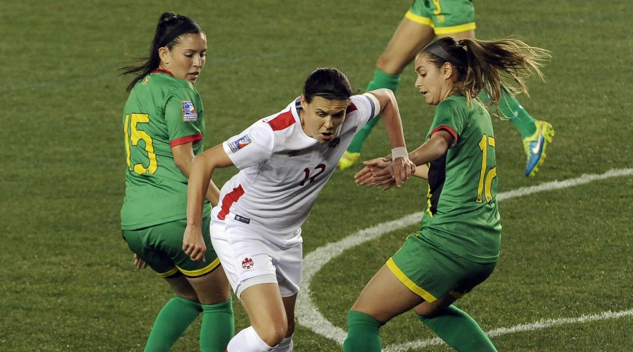 Canada's Christine Sinclair (12) is double-teamed by Guyana's Mariam El-Masri (15) and Olivia Gonsalves (17) during the first half of a CONCACAF Olympic qualifying tournament soccer match Thursday, Feb. 11, 2016, in Houston. (AP Photo/Pat Sullivan)