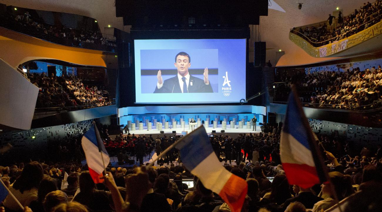 French Prime minister Manuel Valls, projected on a giant screen, delivers his speech during the official presentation of Paris as candidate for the 2024 Olympic summer games in Paris, France, Wednesday, Feb. 17, 2016. Paris, which hosted the Olympics in 1