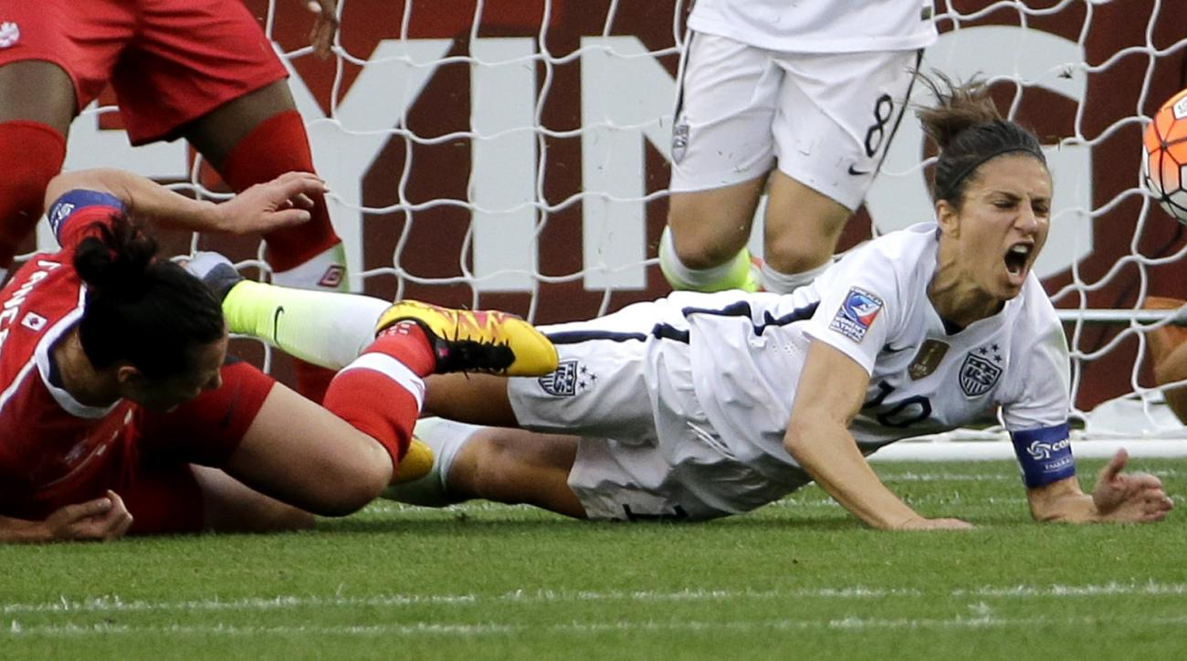 United States' Carli Lloyd, right, falls with Canada's Melissa Tancredi, left, during the first half of the CONCACAF Olympic women's soccer qualifying championship final Sunday, Feb. 21, 2016, in Houston. (AP Photo/David J. Phillip)