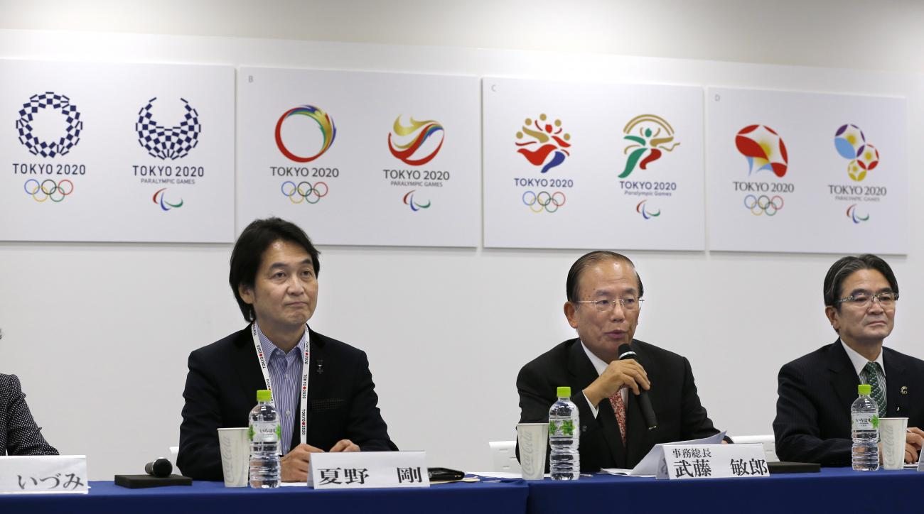 Tokyo 2020 Olympics CEO Toshiro Muto, center, speaks with Tokyo 2020 Emblems Selection Committee Chairperson Ryohei Miyata, right, and Tokyo 2020 Emblems Selection Committee member Takeshi Natsuno as they unveil four designs, in the background, shortliste