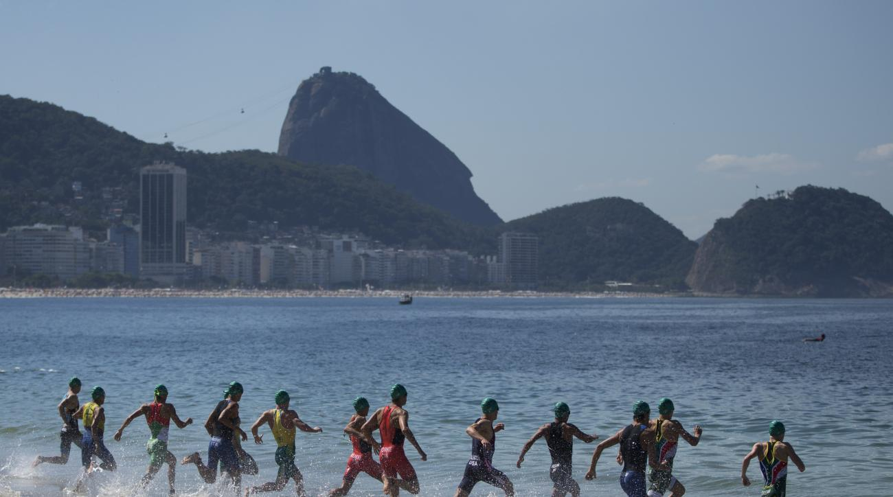 FILE - In this Aug. 2, 2015 file photo, tri-athletes enter the water at the start of the men's triathlon ITU World Olympic Qualification Event on Copacabana beach in Rio de Janeiro, Brazil. Only 50 percent of tickets allocated for Brazilians have been sol