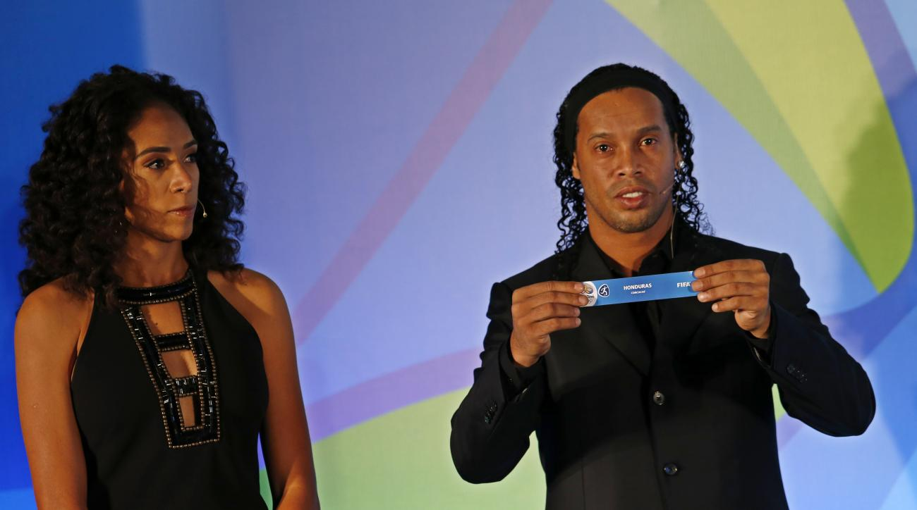 "Brazil's soccer player Ronaldinho holds a paper that reads ""Honduras,"" as he's flanked by former soccer player Aline Pellegrino during the draw for the men's Olympic football tournament in Rio de Janeiro, Brazil, Thursday, April 14, 2016.  (AP Photo/Silvi"